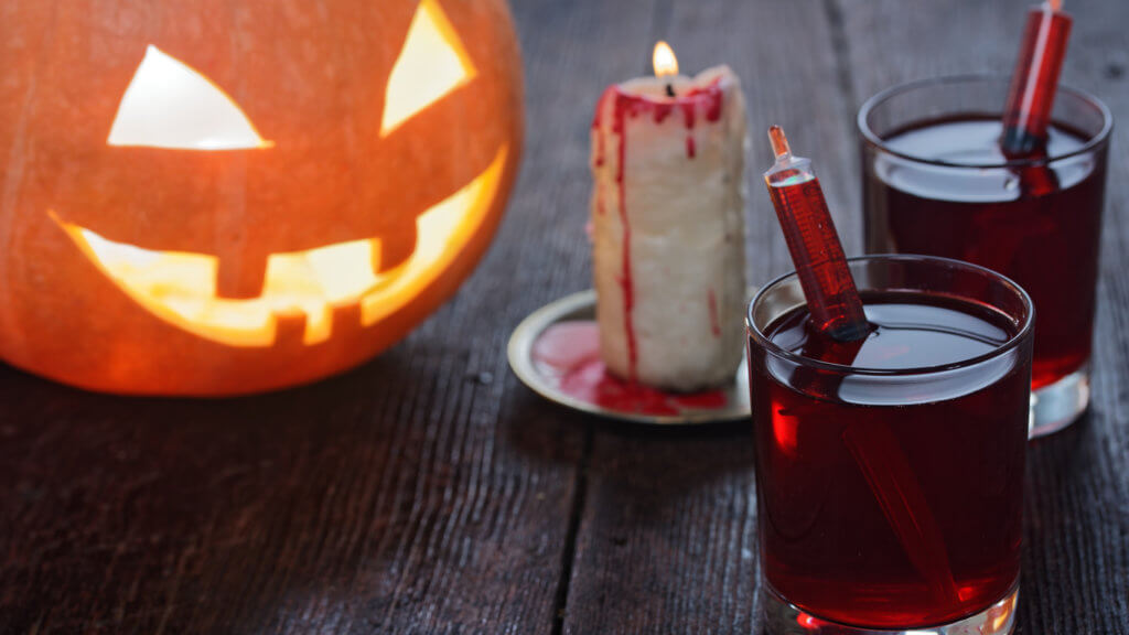 Halloween drink looking like blood served in glasses with syringes. Decoration with natural jack o'lantern and bloody candle. Close-up