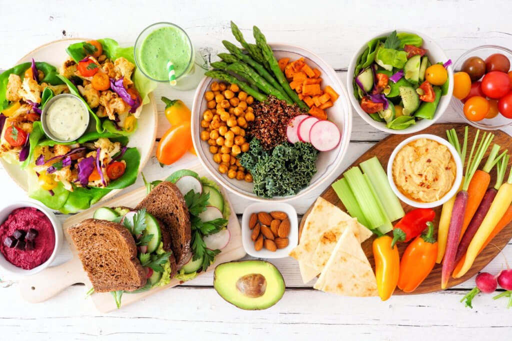 Healthy lunch table scene with nutritious lettuce wraps, Buddha bowl, vegetables, sandwiches, and salad, overhead view over white wood