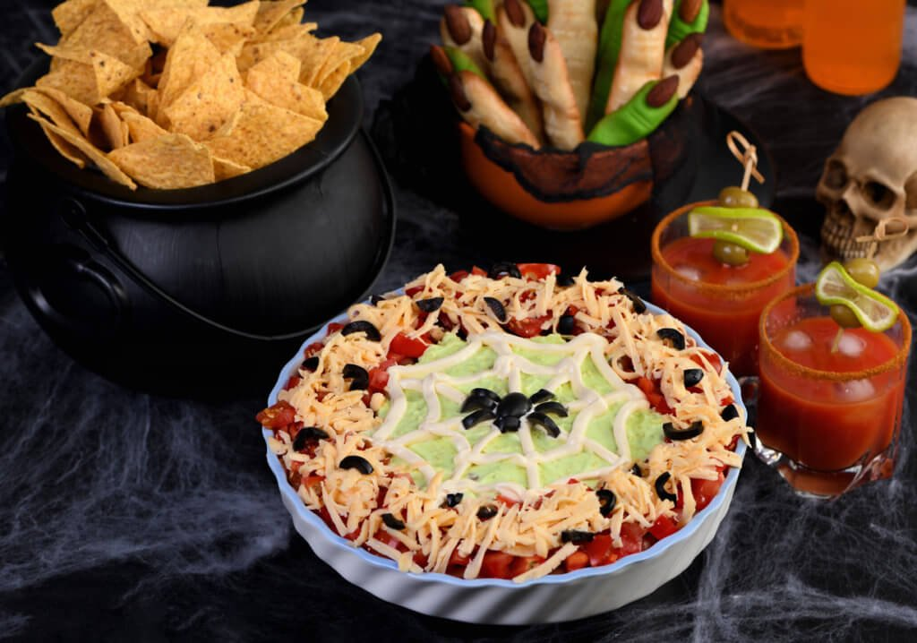 Spooky Halloween Seven Layer Taco Dip: Turn a classic appetizer into a Halloween with of black olive spider .