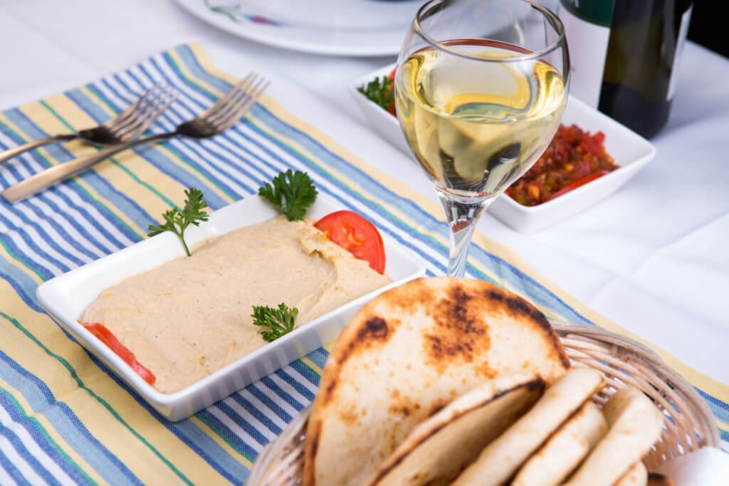 Hummus paired with white wine and pia breads and served on a blue striped cotton placement
