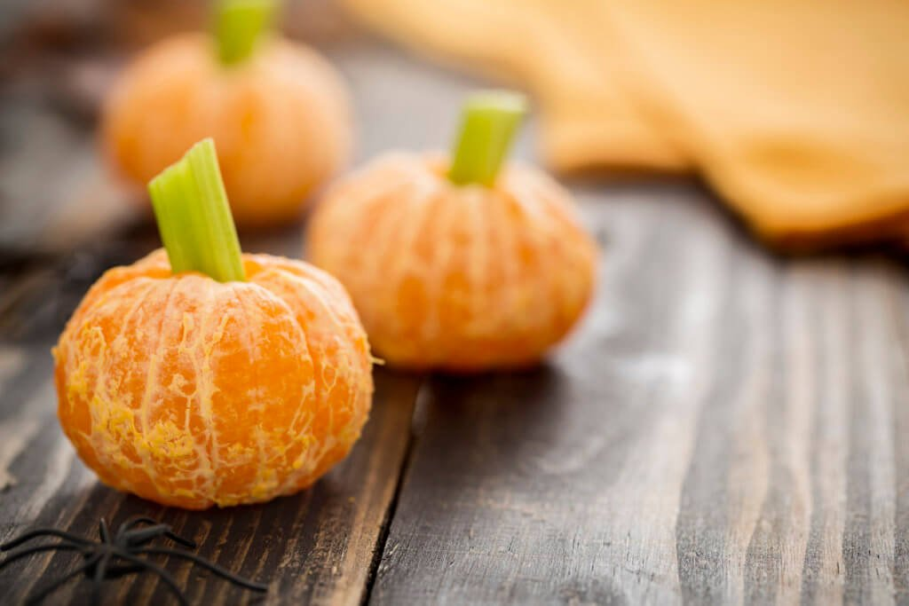 Tangerine jack o'lanterns made of tangerines and celery stick with spider decoration. These healthy halloween are fun food for kids on rustic wood table.