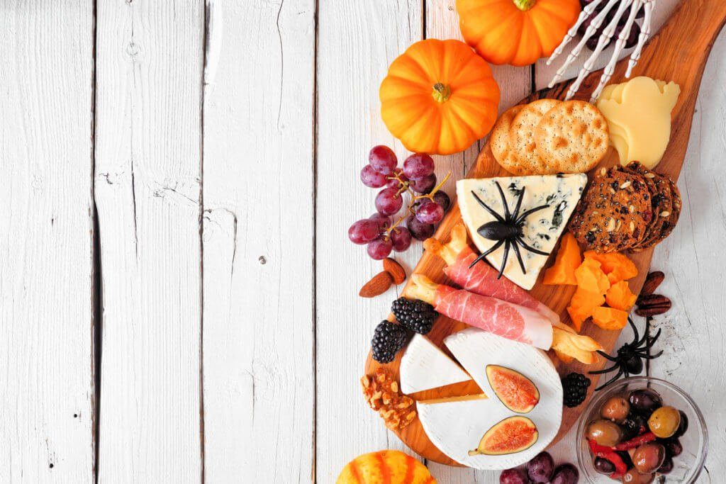 Halloween theme charcuterie side border against a white wood background. Selection of cheese and meat appetizers. Copy space.