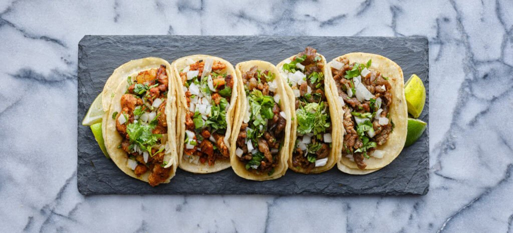 row of mexican street tacos on slate with carne asada and al pastor top down