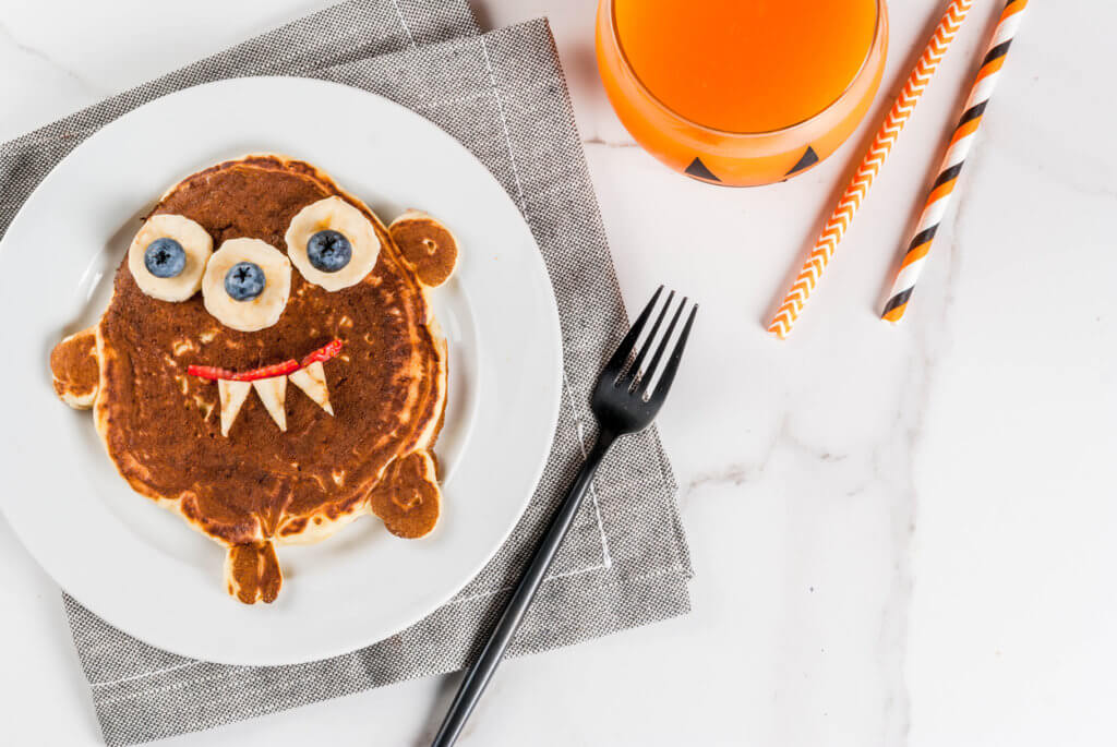 Funny food for Halloween. Kids breakfast pancake decorated like creepy monster, with banana, berries, with pumpkin smoothie juice.