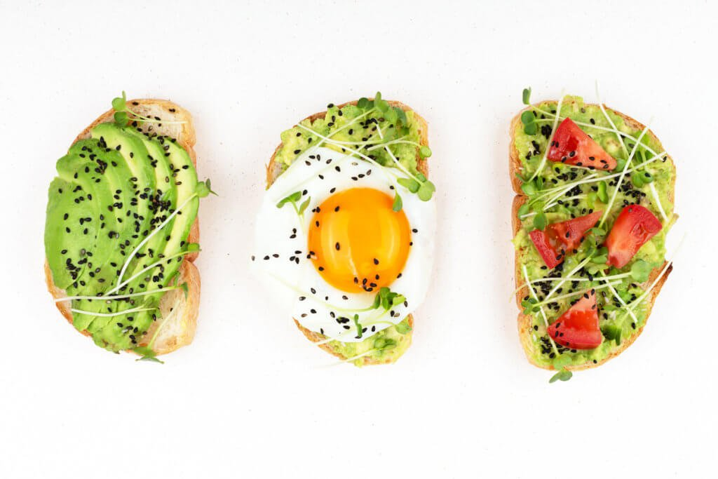 Three healthy toasts with egg, avocado, micro greens and tomatoes.