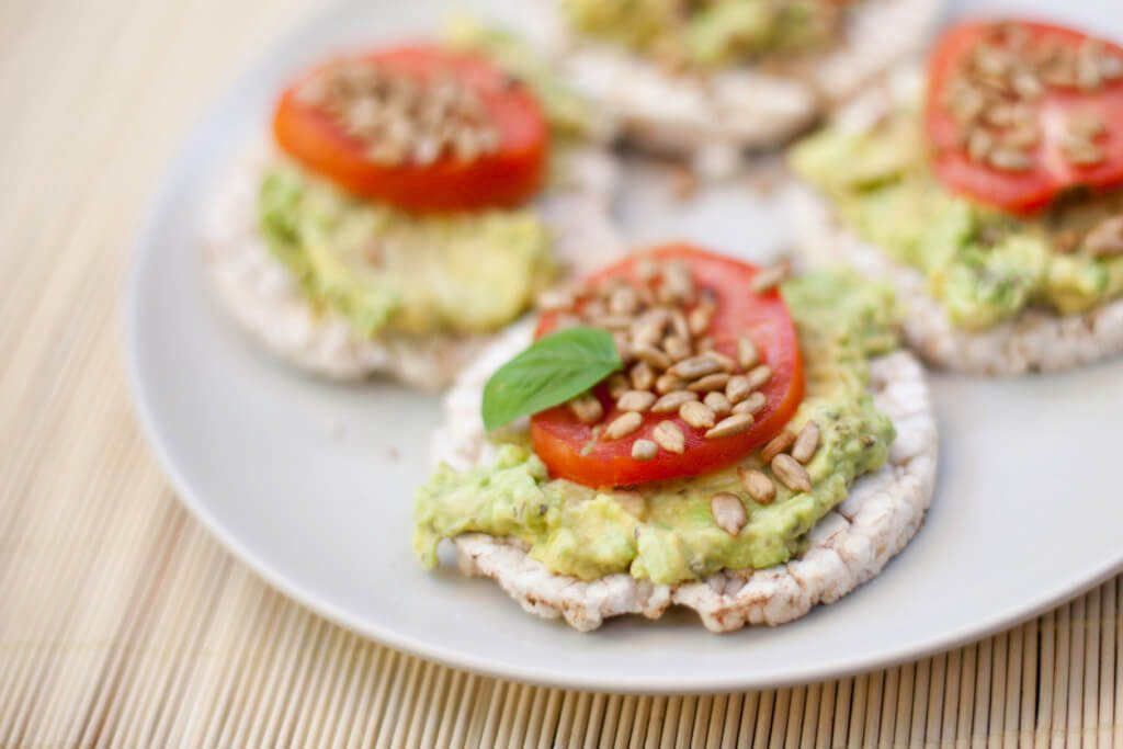 Guacamole, tomatoes on rice cakes.