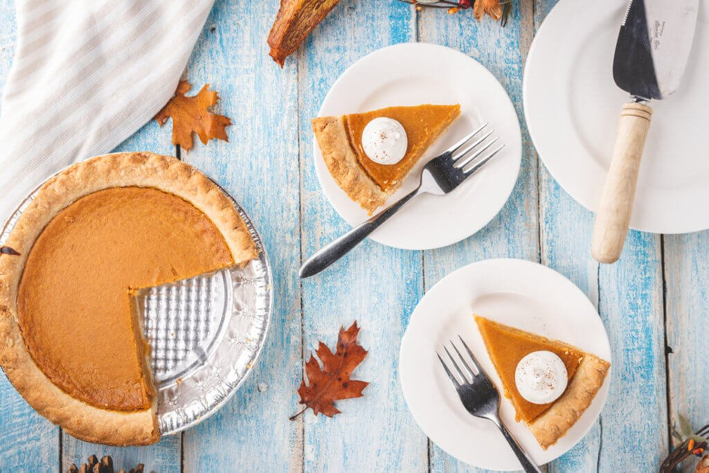 Overhead flat lay shot of a pumpkin pie in a tin with two slices of pumpkin pie on plates with forks.