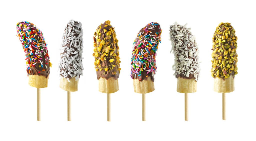 Frozen chocolate dipped banana pops with an assortment of sprinkles, nuts and coconut.