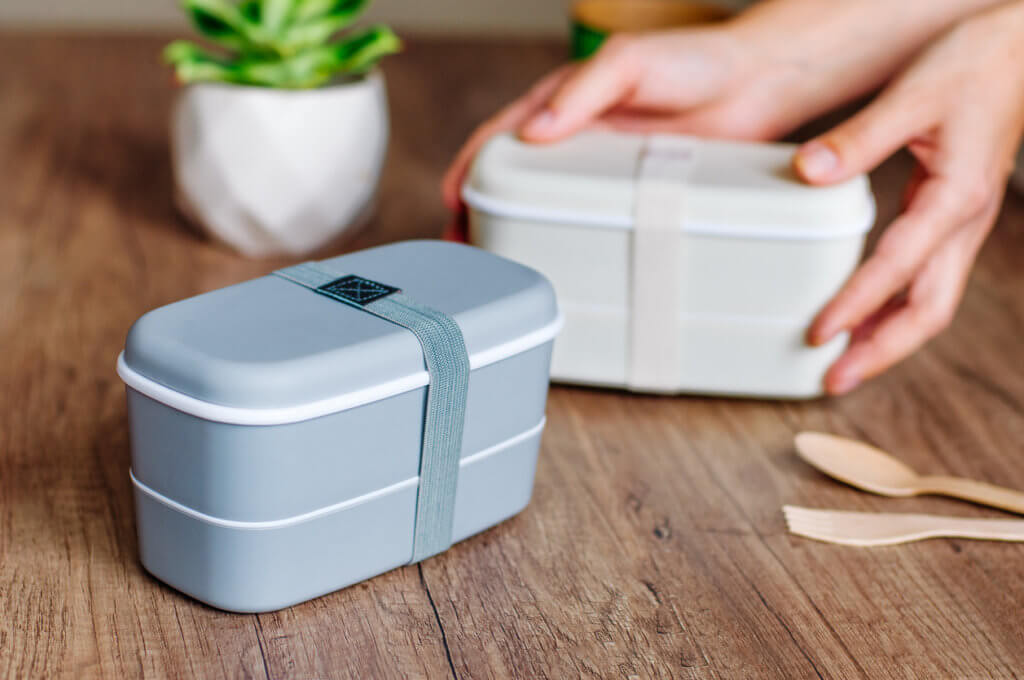 Two closed plastic two-layered lunch boxes with elastic band