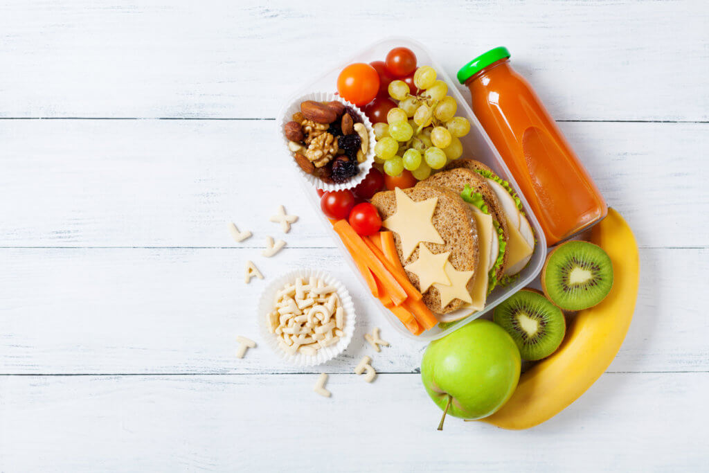School lunch box with vegetables, fruits and sandwich for healthy snack top view.