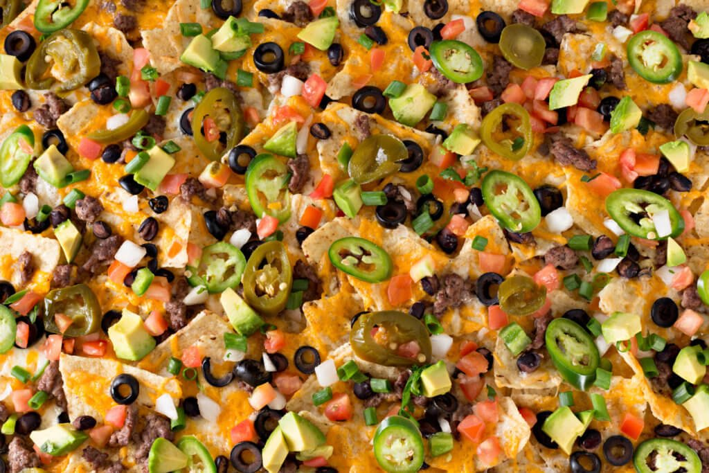 An overhead close up horizontal photograph of some spicy nachos.