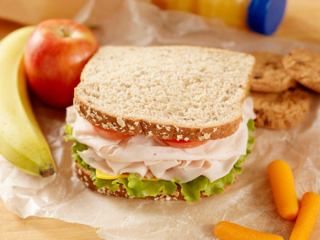 Healthy Packed Lunch with a Turkey, lettuce, Tomato and cheese Sandwich with Fresh fruit, Orange Juice, Baby Carrots and Cookies